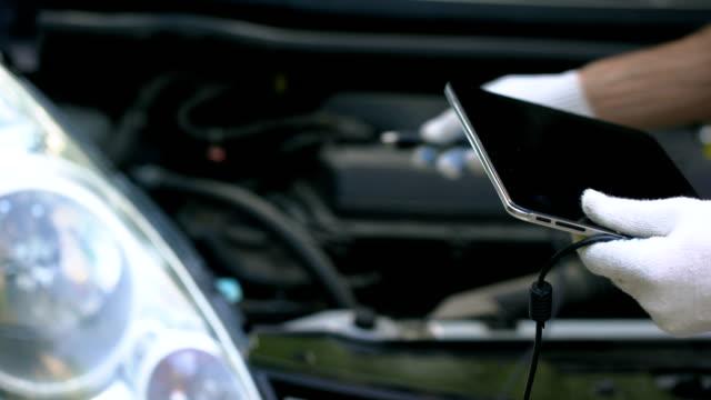 vídeos de stock e filmes b-roll de car diagnostics with tablet, engineer uses computer technologies for auto repair - fundo oficina