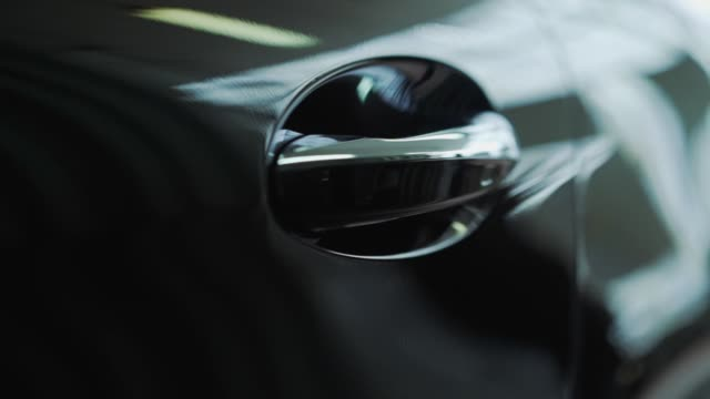 Car door handle close-up. The sunset is reflected in the brand new car. Black car door close-up Car door handle close-up. The sunset is reflected in the brand new car. Black car door close-up. luxury car stock videos & royalty-free footage