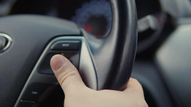 vídeos y material grabado en eventos de stock de el conductor del coche está cambiando los ajustes de la computadora del viaje usando el interruptor en timón - manija