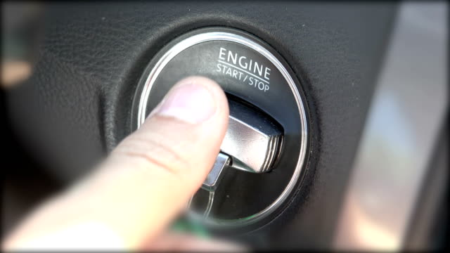 Car driver stopping the engine with modern key fob and taking the key out, closeup video