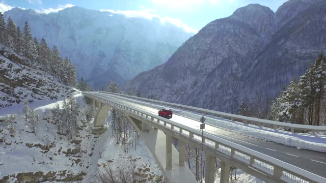 AERIAL: Car drives across mountain viaduct video