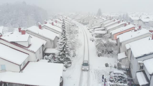 vídeos de stock e filmes b-roll de aerial: car drives down the snowy road leading through the suburban neighborhood - inverno