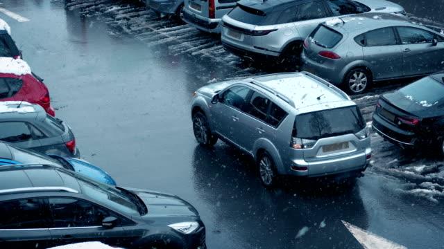 Car Drives In Car Lot During Snowfall video