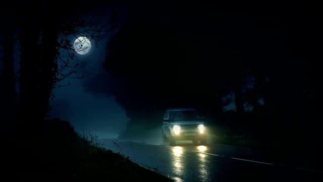 auto guida attraverso spaventoso bosco con luna piena - passare davanti video stock e b–roll
