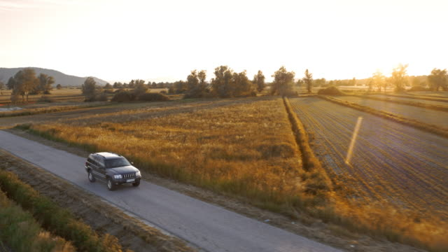 AERIAL Car driving along a countryside road in sunset