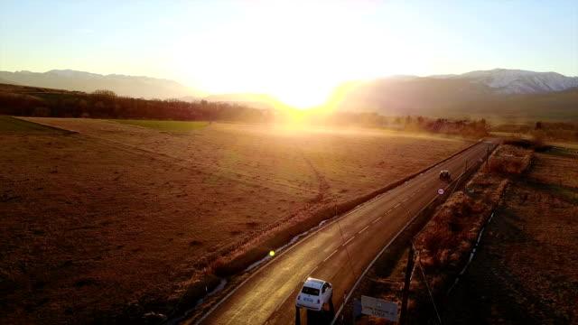 Coche conducir a lo largo de un camino de campo en la puesta de sol - vídeo