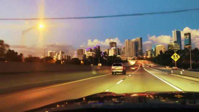 WS POV car driving along freeway at night toward city, Miami, Florida, USA