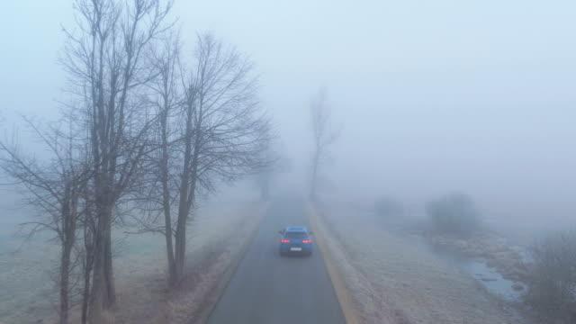 stockvideo's en b-roll-footage met antenne: auto rijden langs enge mistig landweg door de mistige velden - mist donker auto