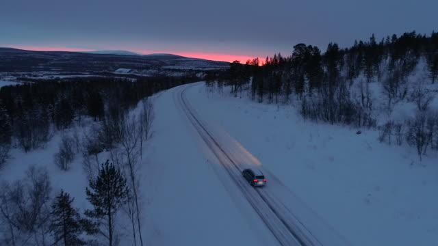 antenn: bil körning längs snötäckta berg highway genom tallskog vid solnedgången - pink sunrise bildbanksvideor och videomaterial från bakom kulisserna
