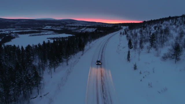 AERIAL: Car driving along snowy mountain highway through spruce forest at sunset