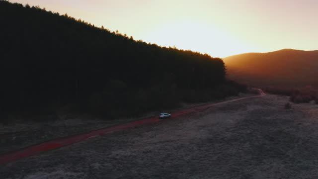 vídeos de stock, filmes e b-roll de carro suv dirigindo ao longo da estrada rural vazia ao pôr do sol dourado - largo descrição geral