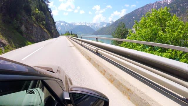 car pov: driving alongside lake achensee, austria - stato federato del tirolo video stock e b–roll