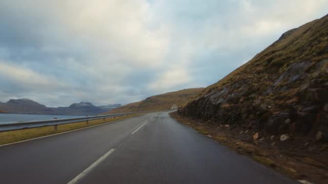 vídeos de stock e filmes b-roll de pov car driving at faroe islands: winter roads - reto descrição física