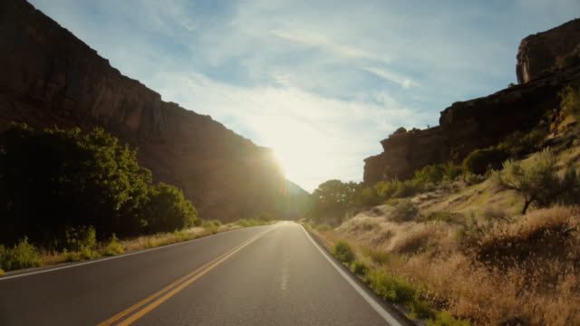 pov car driving in usa southwest: straight road and majestic sunset outdoors - viaggio in macchina video stock e b–roll