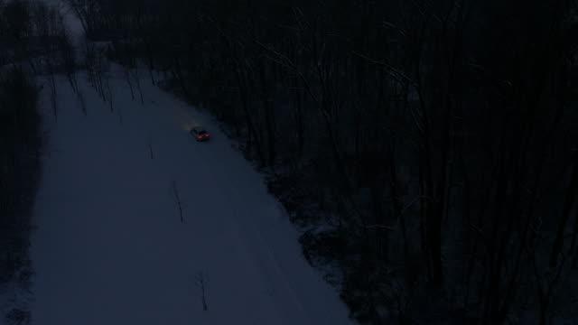 stockvideo's en b-roll-footage met luchtfoto auto rijden op een landweg nachts - mist donker auto