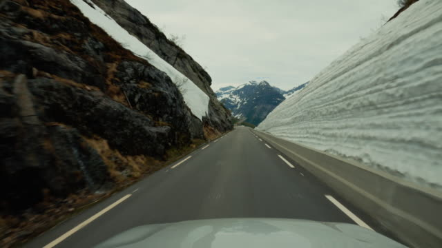 pov car driving on a mountain pass in norway: outdoors roadtrip in the snow - passo montano video stock e b–roll