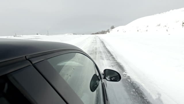POV of car driving on mountain snow road at day video