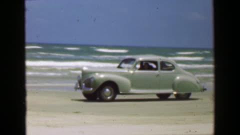 vidéos et rushes de 1952: voiture sur le sable de plage océan devant le fracas des vagues de surf. - vintage