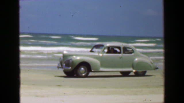 1952: Car driving on ocean beach sand in front of crashing surf waves. video
