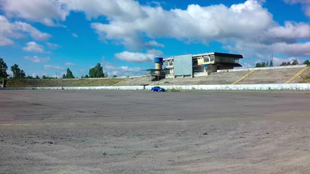 vídeos y material grabado en eventos de stock de coche en el círculo de la carrera en autódromo abandonado con fondo de cielo azul - nieve amontonada