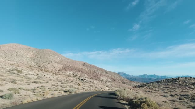 vídeos de stock e filmes b-roll de car driving on road on sunny day in death valley national park. california, usa - parque nacional do vale da morte