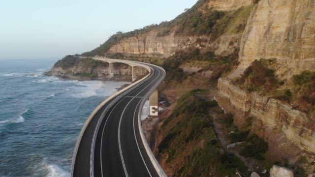auto che guida sul sea cliff bridge lungo l'autostrada rocciosa australiana tortuosa - strada tortuosa video stock e b–roll