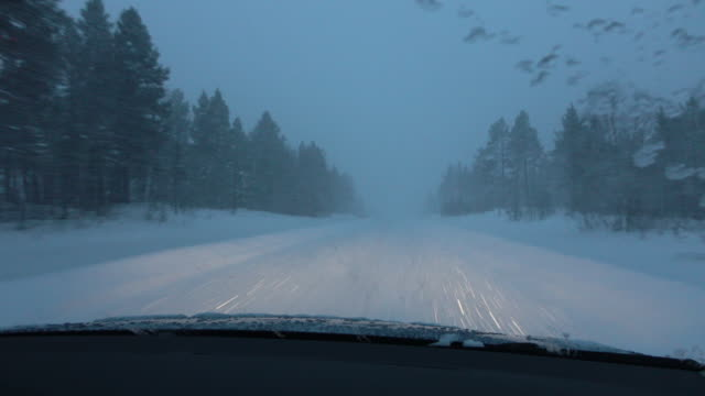 POV Car driving on slippery snowy country road during heavy snowstorm in Finland video