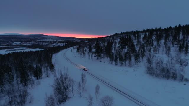 antenn: bil körning på snöiga berget motorväg genom tallskog vid soluppgången - pink sunrise bildbanksvideor och videomaterial från bakom kulisserna