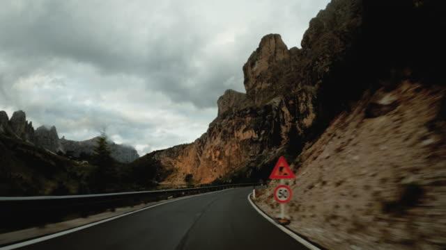 auto pov in auto sulle dolomiti: maestoso passo di montagna leggero al tramonto - strada tortuosa video stock e b–roll