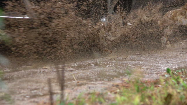 SLOW MOTION CLOSE UP: SUV car driving over deep rain puddle on dirt road SLOW MOTION CLOSE UP: Detail of a SUV car tyre driving over deep puddle and splashing water across the dirt road. Black SUV car tires driving on wet dirt road after rain and over muddy puddle. mud stock videos & royalty-free footage
