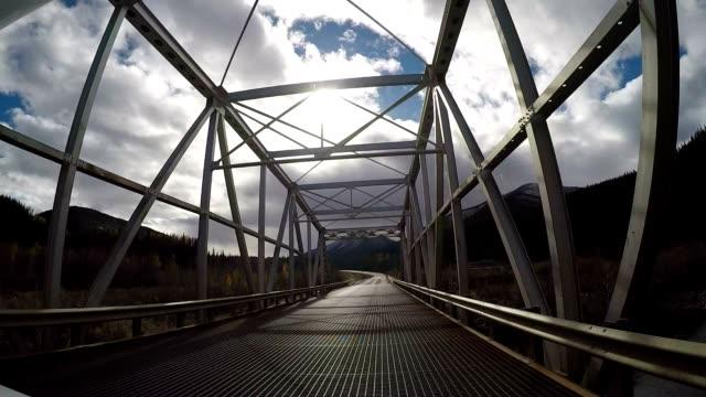 Car driving over suspended bridge in Canada POV video