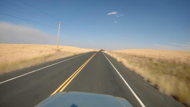 道路の両側に干し草畑を持つ田舎を運転する車のPOV ビデオ