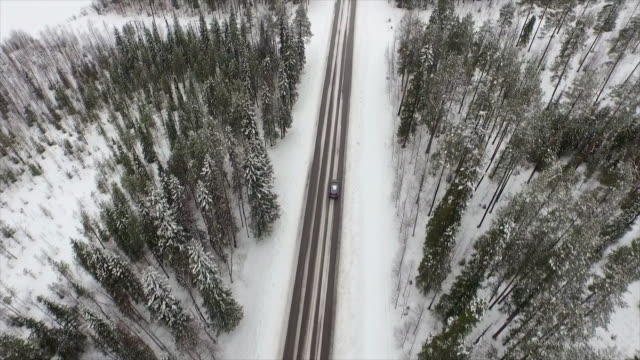 AERIAL: Car driving through Finnish snowy woods A silver car is driving through the woods in north of Finland on a winter day. The trees are covered with snow and the lake is frozen. The road never seems to end. vinter stock videos & royalty-free footage