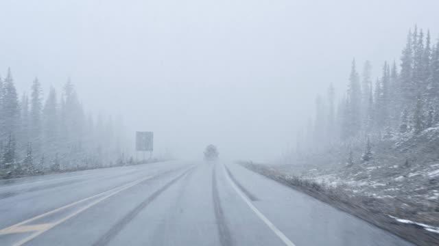 vidéos et rushes de véhicule conduisant avec la neige lourde dans le blizzard avec la mauvaise visibilité au stationnement national - blizzard
