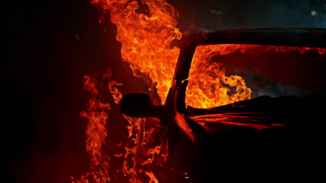 slo mo ld car engulfed by billowing flames at night - bruciato video stock e b–roll