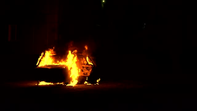 car engulfed in flames of fire and burning at night - ribellione video stock e b–roll