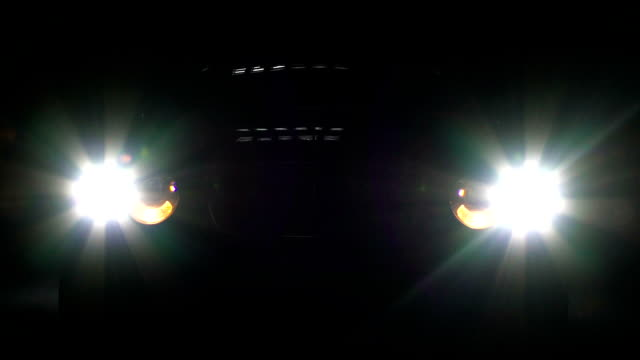 Car headlamps switch on and off in darkness, bright headlight illumination