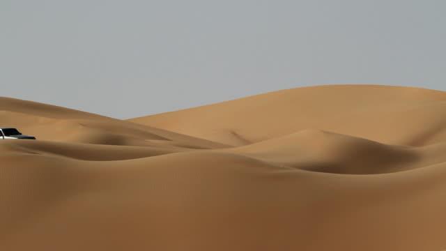 car in the dunes of desert video