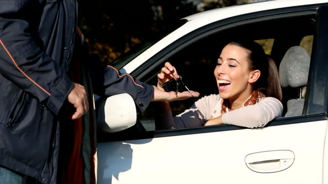Car kay Smiling Teenage Girl sitting in the car and male Car seller giving to her a  car key. car key stock videos & royalty-free footage