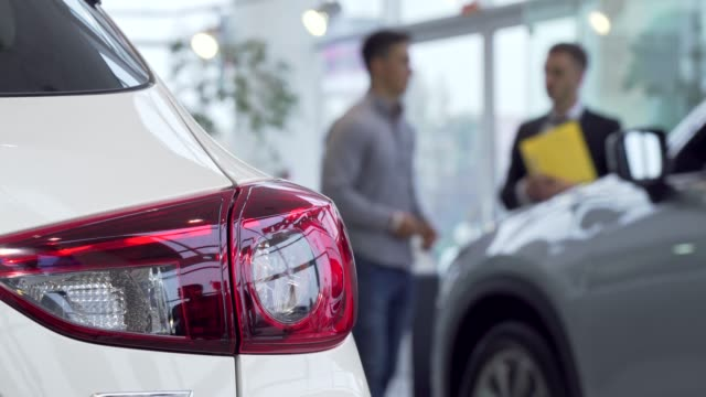 Car lights on the foreground, man buying car at the dealership on the background Car lights on the foreground, man buying car at the dealership on the background. Selective focus on a car, salesman helping male customer on the background. Buying car concept car salesperson stock videos & royalty-free footage
