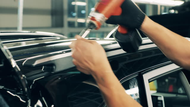 Car manufacturing worker assembling a car roof. Close up video