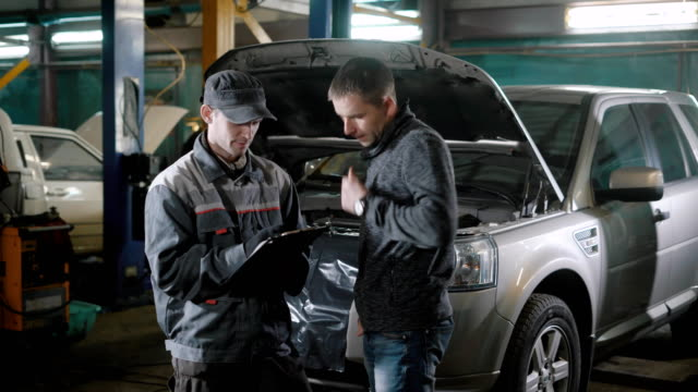 Car mechanic and customer near car Car mechanic standing near customer and car in repair shop and filling in information. form filling stock videos & royalty-free footage