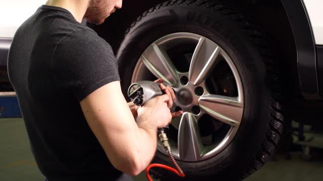 Car mechanic changing car wheel in auto repair garage video