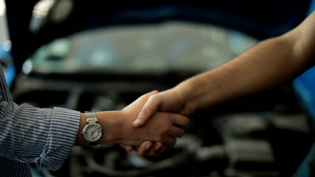 Car mechanic handshakes customer video