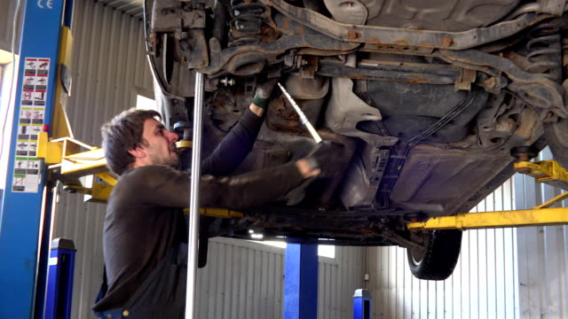 car mechanic with spanner tighten car of lifted automobile at repair service - leva video stock e b–roll