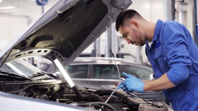 car mechanic with wrench working at auto repair shop - затягивание стоковые видео и кадры b-roll