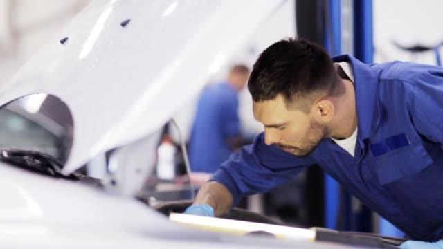bilmekaniker med skiftnyckel arbetar på bilverkstad - reparera bildbanksvideor och videomaterial från bakom kulisserna
