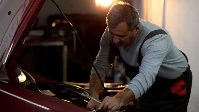 Car mechanic working in garage video