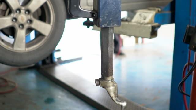 kfz-mechaniker arbeiten unter einem fahrzeug. - steckschlüssel stock-videos und b-roll-filmmaterial