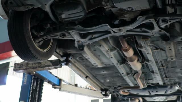 vídeos y material grabado en eventos de stock de mecánico trabajando bajo un vehículo. - llave tubular